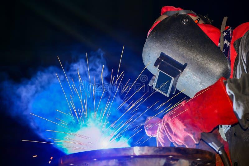 Röret för stål för branscharbetaren tänder det svetsande med gnistor i fabrik på svart bakgrund royaltyfri foto