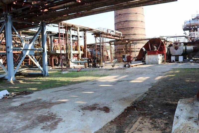 Rörledningplanskild korsning med järnrör för att pumpa flytande mot bakgrunden av ett stort tegelstenrökrör på ett oljeraffinader royaltyfri bild