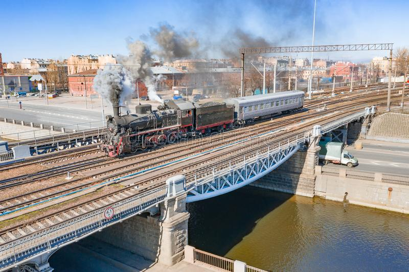 Rörlig retro ånga med en passagerarevagn passerar över en bro över en kanalflod i den historiska delen av staden royaltyfri fotografi