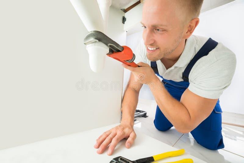 Rörmokare Fixing Sink Pipe med den justerbara skiftnyckeln arkivbild