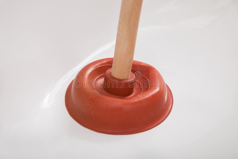 Rörmokare som använder dykaren i vask royaltyfri fotografi