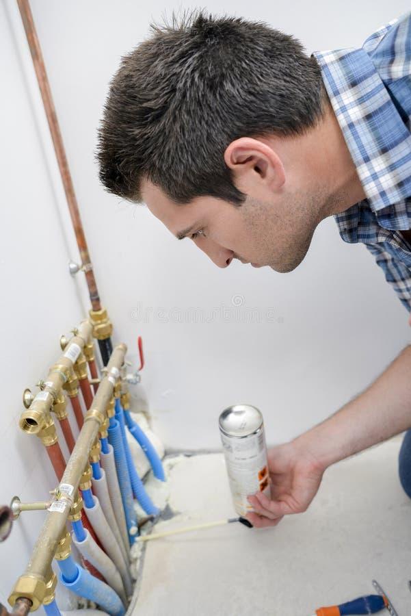 Rörmokare som kontrollerar leda i rör systemet arkivfoton