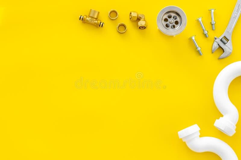 Rörmokarearbete med instrument, hjälpmedel och kugghjulet på gul modell för bästa sikt för bakgrund royaltyfri fotografi