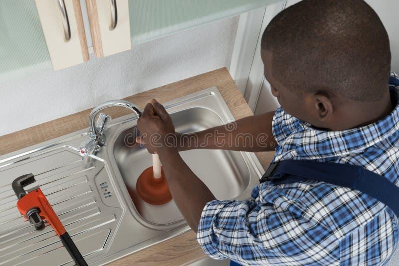 RörmokareCleaning Sink With dykare arkivfoto