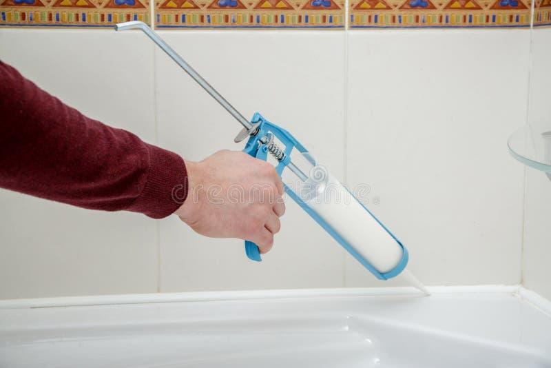 Rörmokarehand som applicerar silikontätningsmedel i badrummet royaltyfri foto