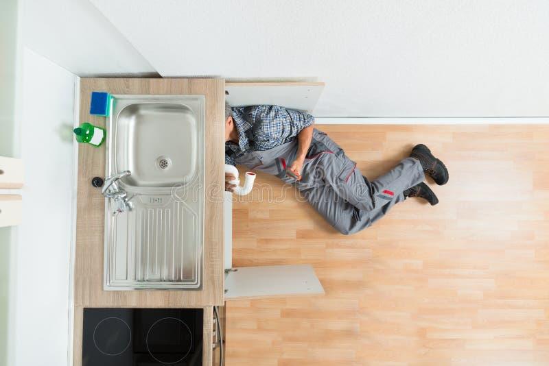 RörmokareWorking Under Kitchen vask arkivbilder