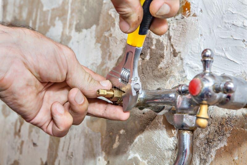 Rörmokeriarbeten, reparationsvattenkran, justerbar skiftnyckel för closeup i hand royaltyfri bild
