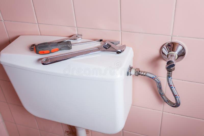 Rörmokerihjälpmedel som ligger på toalett royaltyfri fotografi