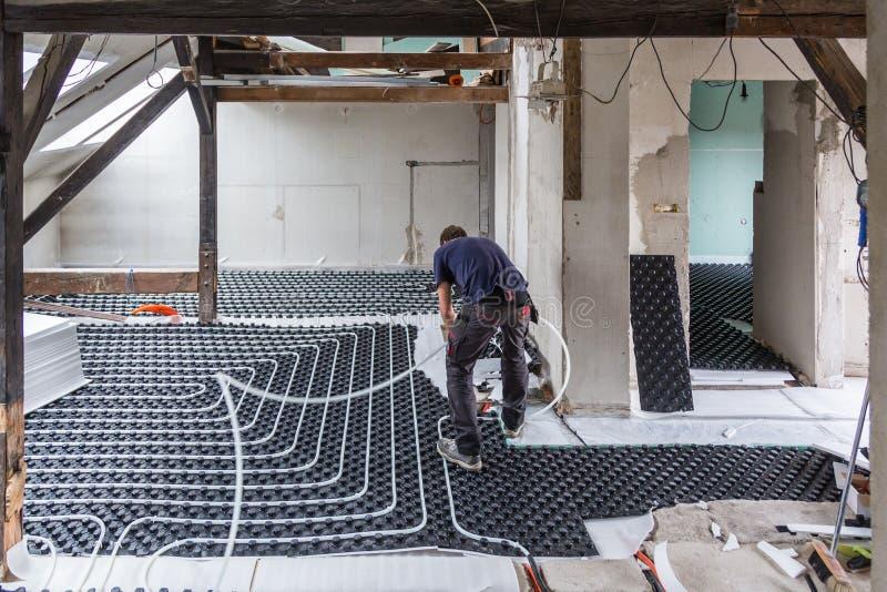 Rörmontör som monterar underfloor uppvärmning royaltyfri foto