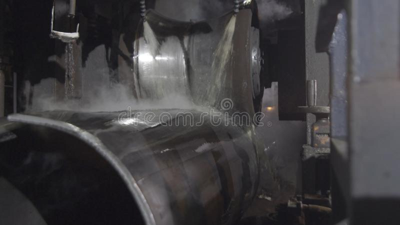 Rörrullningsprocess på produktionsanläggningen Closeup av produktionsprocessen av metallröret Industriellt maskineri i skurkroll arkivfoto
