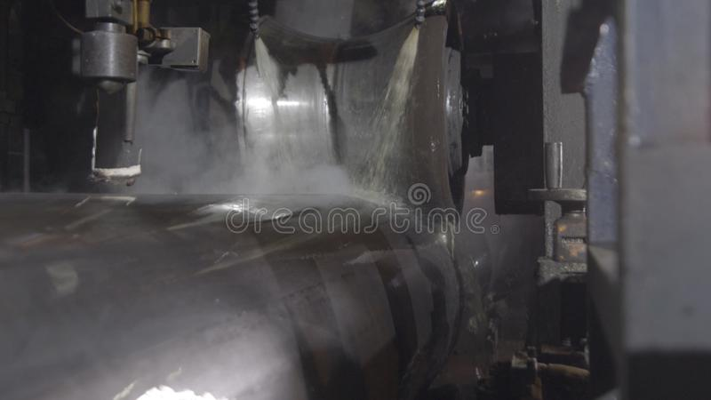 Rörrullningsprocess på produktionsanläggningen Closeup av produktionsprocessen av metallröret Industriellt maskineri i skurkroll royaltyfri fotografi