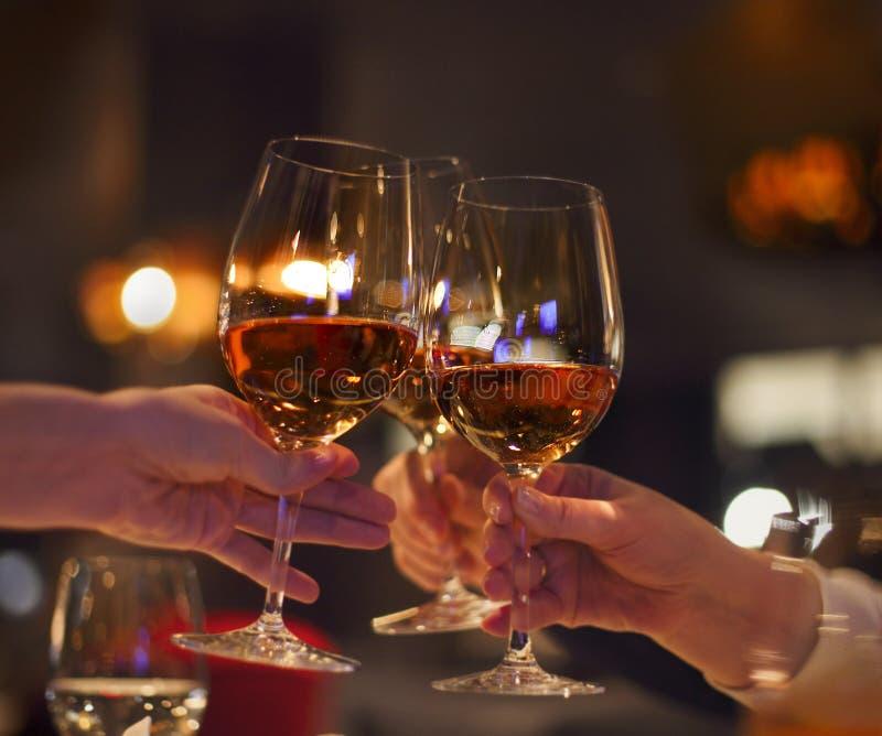 Rösten Sie im Restaurant mit vollen Gläsern rosafarbenem Wein stockbild
