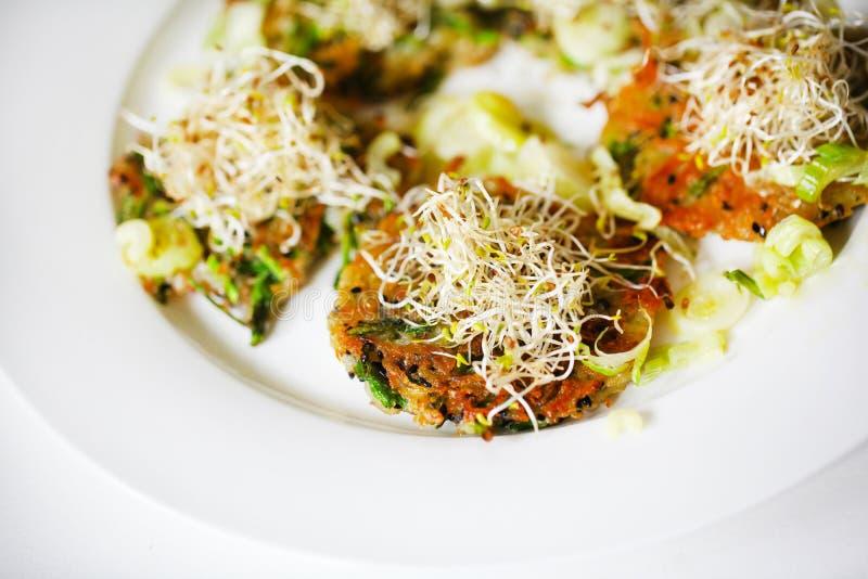 Rösti ou pommes de terre rissolées de pomme de terre, avec l'asperge, les graines de sésame et les pousses sauvages photo stock