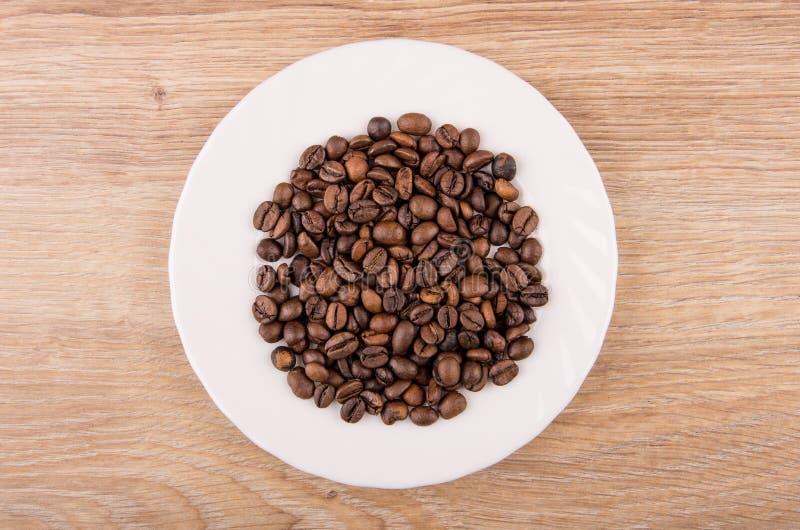 Röstkaffeebohnen in der weißen Platte auf Holztisch stockbild