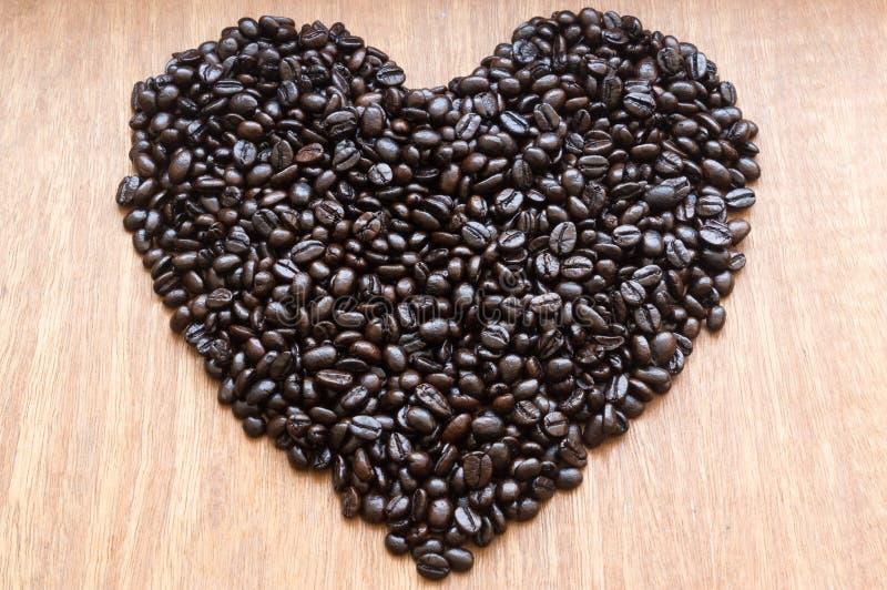 Röstkaffeebohnen im Herzen formen auf rot-grauen hölzernen Hintergrund stockfoto