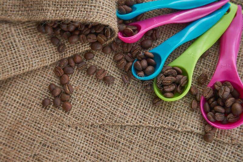 Röstkaffeebohnen, Messlöffel der Dosis auf Jutefasersack stockbild