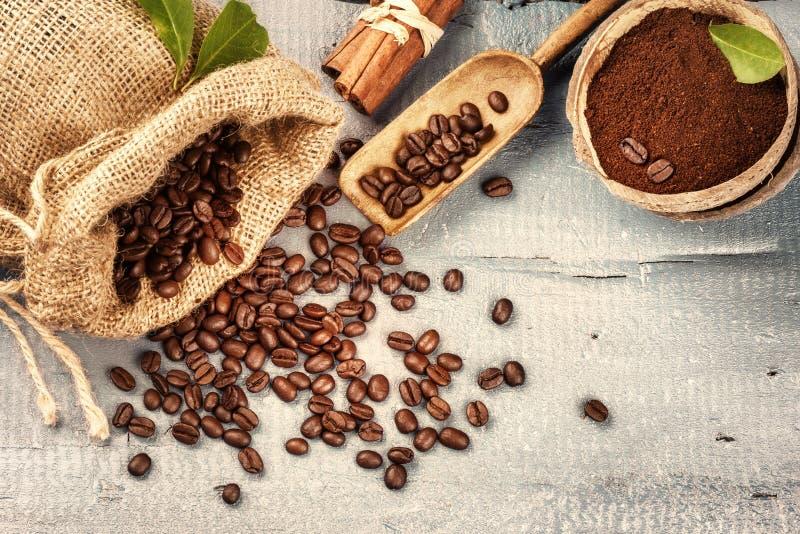 Röstkaffeebohnen mit gemahlenem Kaffee und Zimtstangen auf w lizenzfreie stockfotos