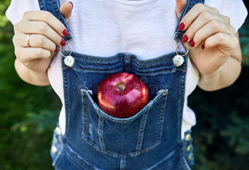 Rött äpple i jeansoverallerna royaltyfri foto