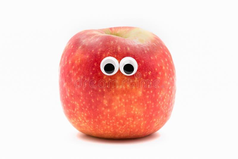 Rött äpple med googly eyesy på vit bakgrund - fruktframsida royaltyfria foton