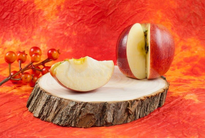 Rött äpple med skivan på stubbeavsnitt på härlig kulör apelsin- och gulingbakgrund royaltyfri fotografi