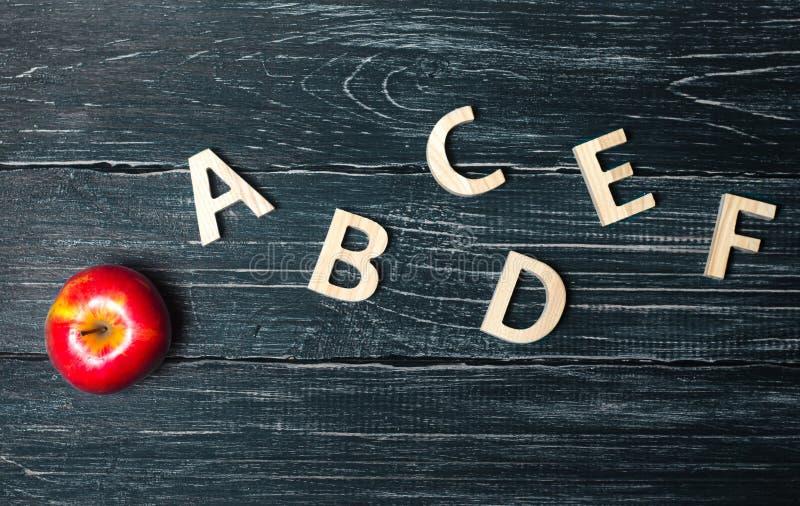 Rött äpple och alfabet som göras av träbokstäver på en mörk backgrou royaltyfria foton