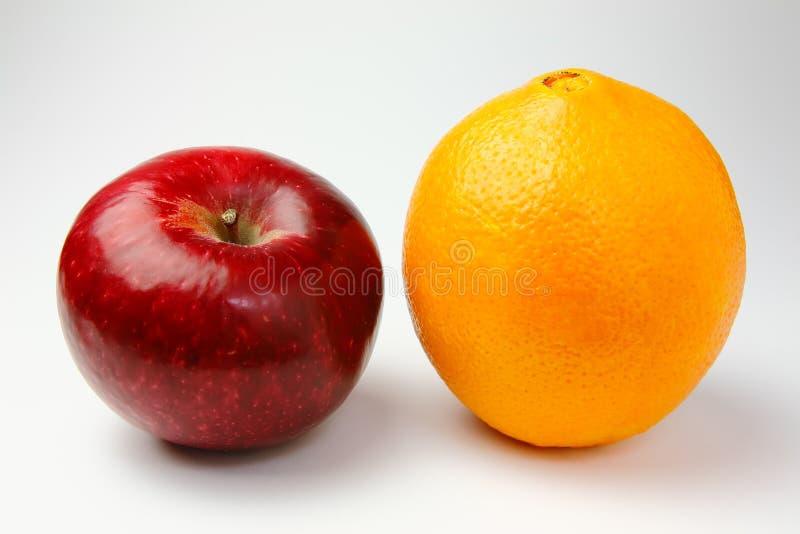 Rött äpple och apelsin royaltyfria foton