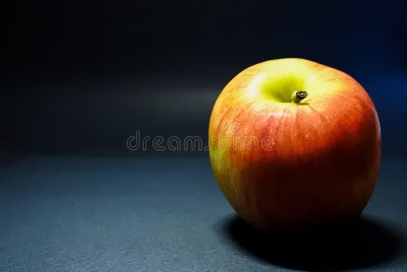 Rött äpple på den mörka bakgrunden royaltyfri foto