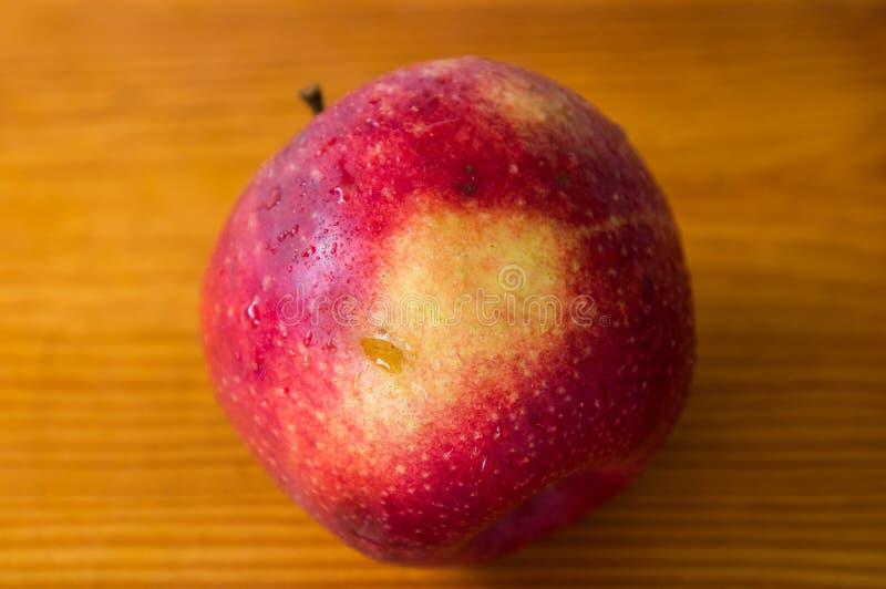 Rött äpple på ett trägrått bräde royaltyfria bilder