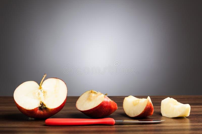Rött äpple på tabellen med den skivade stycken och kniven, grå bakgrund royaltyfri bild
