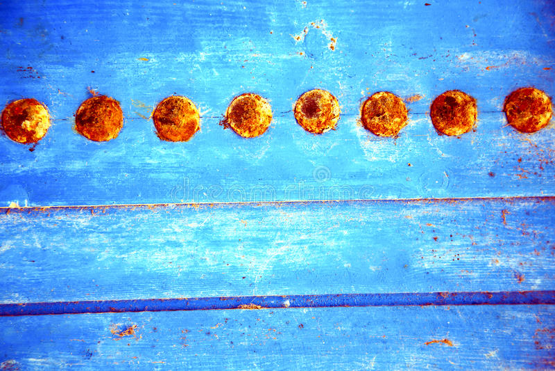rött avriven målarfärg i blå wood dörr och rostigt spikar fotografering för bildbyråer