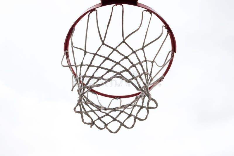 Rött basketbeslag, korg mot vit himmel utomhus- basketdomstol arkivfoton