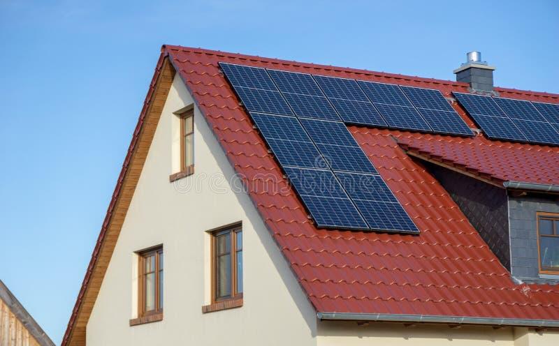 Rött belagt med tegel tak av ett nytt hus med solpaneler eller den photovoltaic kraftverket fotografering för bildbyråer