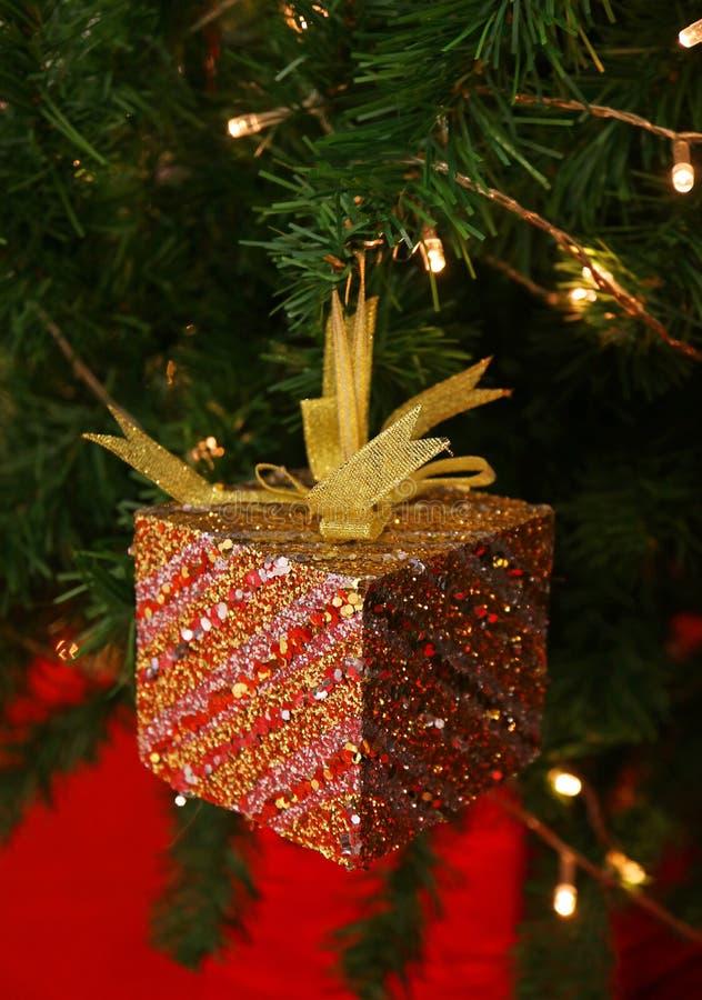 Rött blänka fyrkantiga Mini Gift Box med den guld- bandpilbågen som hänger på den mousserande julgranen arkivbild