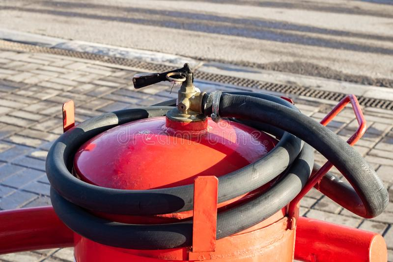Rött brandsläckare- och slangslut upp arkivfoton