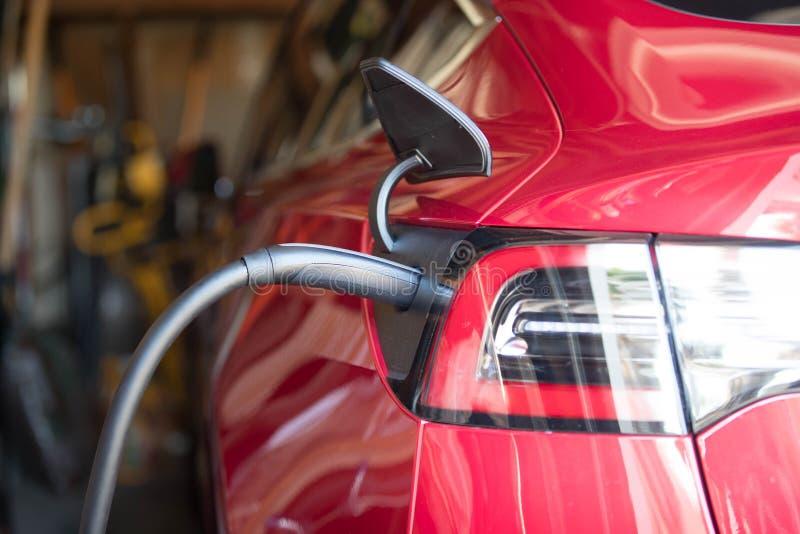 Rött elektriskt medel pluggat in garage royaltyfri fotografi