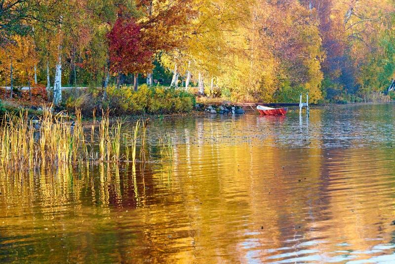 Rött fartyg på en kust av en höstsjö med gula och röda träd som reflekterar i vatten royaltyfri foto