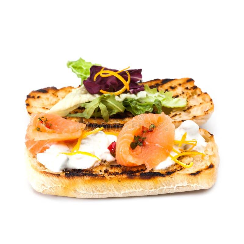 Rött fiskrostat bröd med sallader och ostsås Klassisk mediterrian grillat bröd för matlax smörgås, marinerat kött arkivfoton