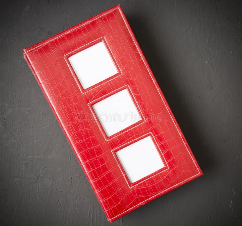 Rött fotoalbum med tomma fotoramar, fotohörn, utrymme för fri kopia arkivfoto