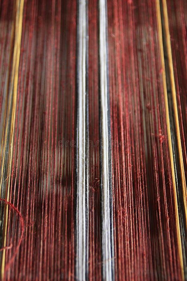 Rött garn på vävstolen royaltyfria foton