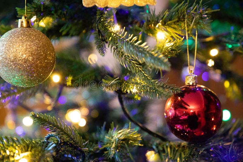Rött garneringjordklot på slut för julträd upp arkivfoton