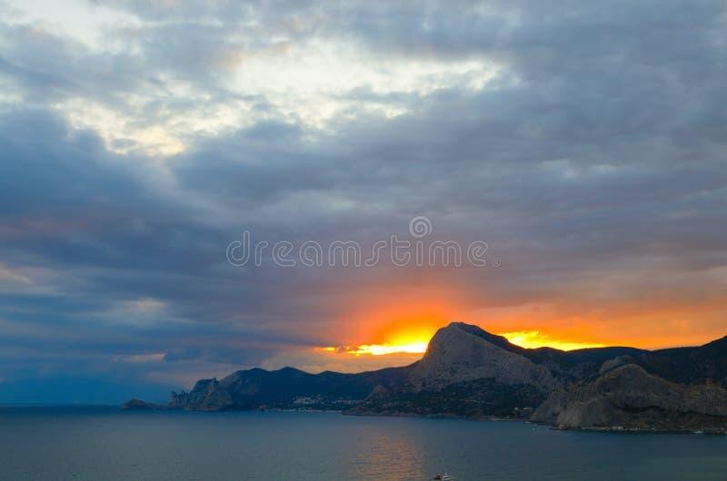 Rött glöd i himlen över berget på solnedgången på Blacket Sea i Krim, Sudak royaltyfria bilder