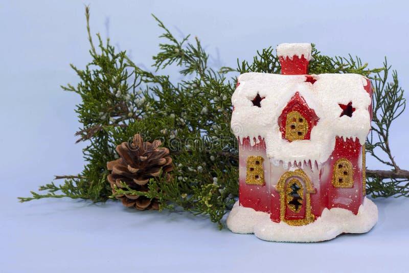 Rött gulligt hus i snön nära enfilialen och att sörja kotten på ett ljust - blå bakgrund kopiera avst?nd fotografering för bildbyråer