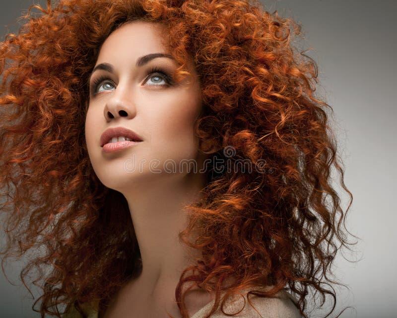 Rött hår. Härlig kvinna med lockigt långt hår. arkivfoto