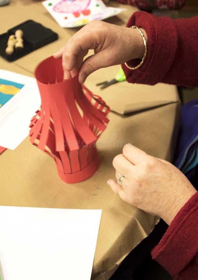Rött hantverk för pappers- lykta som är show vid mormorhänder royaltyfria bilder