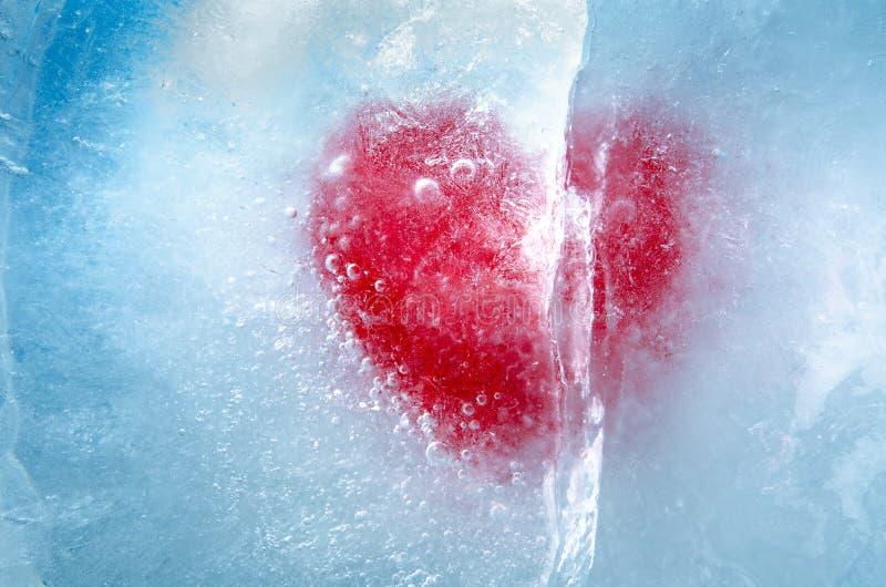 Rött hjärta fryst i is med stor spricka, en symbol för kärlek eller svek eller separation royaltyfri foto