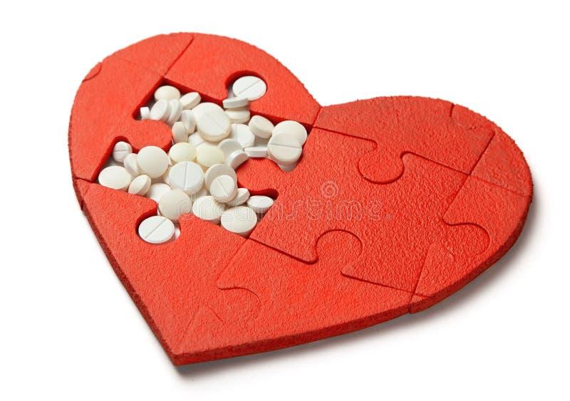 Rött hjärtapussel och vita piller som isoleras på vit bakgrund Begreppsbehandling av hjärtsjukdompreventivpillerar royaltyfri foto