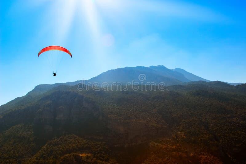 Rött hoppa fallskärm i himlen ovanför bergen royaltyfria foton