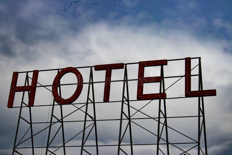 Rött hotelltecken med molnig himmel royaltyfria foton