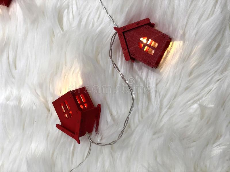 Rött hus med strålar av ljus på en fluffig filt arkivfoton