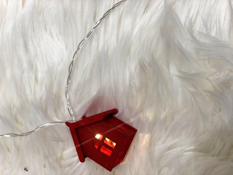 Rött hus med strålar av ljus på en fluffig filt royaltyfri bild